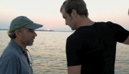 two men standing by the water
