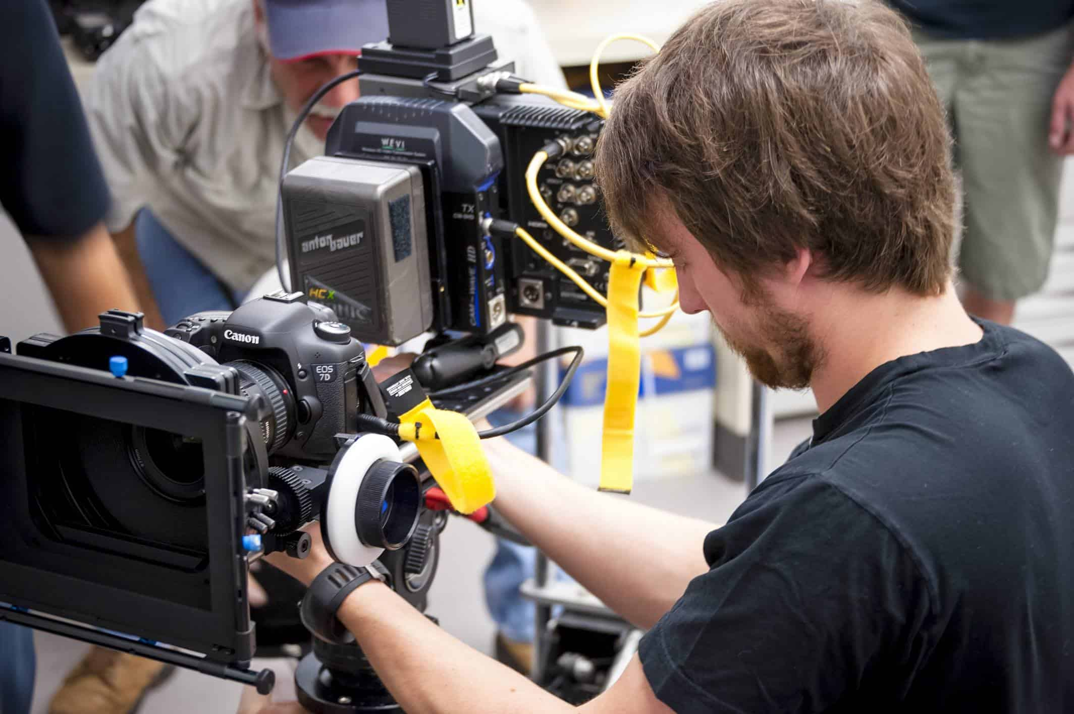 man working on a video camera